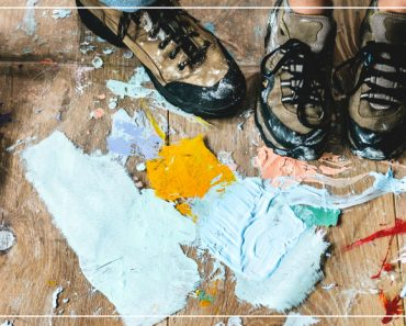 paint splattered on the floor with a man and women's hiking shoes