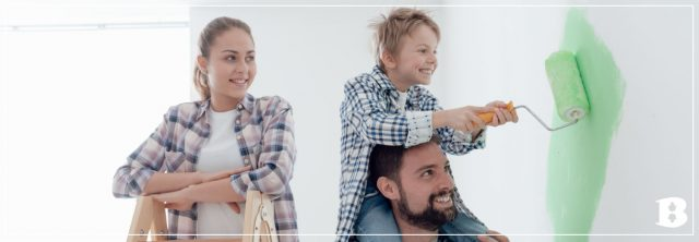 family painting a white wall green with happy kid on dad's shoulers