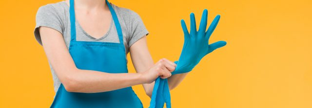 woman with apron putting on gloves with bright yellow background