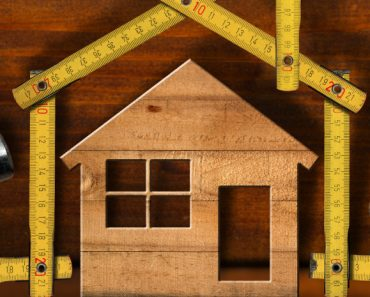 wooden house with tools and measuring tape surrounding it