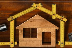little wooden house with tools and measuring tape surrounding the house