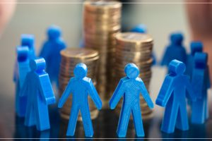 hands protecting a group of blue plastic people surrounding a stack of coins
