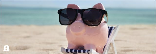 piggy bank in a chair with sunglasses on a beach