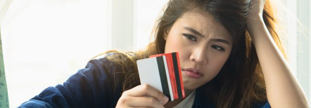 girl looking upset at her credit cards