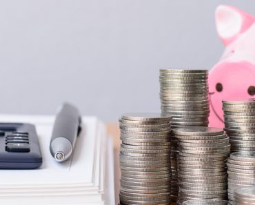smart piggy with calculator, stacks of coins and a stack of paper