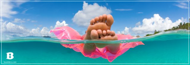 feet on a pink floaty in a bright clear ocean