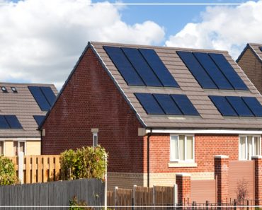 rows of brick homes with solar power panels on the roof
