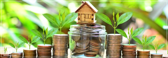 little wooden home on top of a jar of change with stacks of change leading up to the jar on both sides