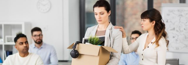 woman in office with box of belongings and co-worker sad for her.